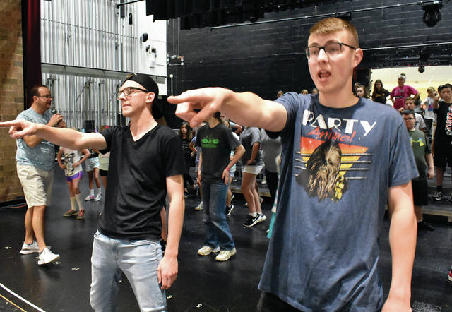 Piqua Show Choir veterans Ryan Barr, left, and David Potts, lead Music Warehouse participants in a dance number as Tom Westfall, far left, provides direction and encouragement. This year's Music Warehouse has 89 participant who will cap off a week of hard work with a Friday night performance at Piqua High School beginning at 7:30. The event is open to the public.