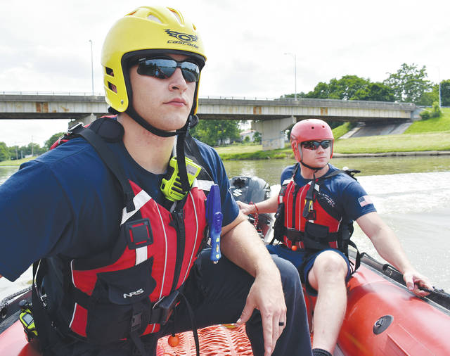 "Piqua firefighters Corbin Peltier and Tony Sutter line up their boat to ""rescue"" firefighter Doug Stewart at the Great Miami River in Piqua on Thursday. Piqua Fire Department Shift 1 spent the afternoon doing water rescue training on the river. ©2019 Miami Valley Today. All rights reserved"