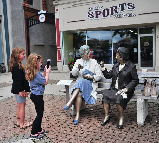 Allison Hewitt, 9, and her sister Miranda, 5, check out one of Troy's Sculptures on the Square soon after it was put in place in front of Troy Sports Center on Thursday.