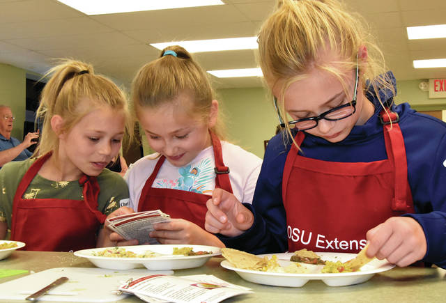 Margaret Adams, 9, Layton Rush, 10, and Evelyn Adams, 11, all of Bethel Township, read their recipe book as they work on making tortillas on Mexican food day at Miami County Jr. Chef Camp at the Elizabeth Township Community Center on Tuesday. There are 94 campers taking part in this year's camp. During the three day event, campers will learn to prepare and sample foods from Mexico, Italy, and Japan.