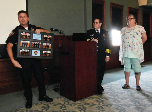 Deputy Chief Marty Grove of the Piqua Police Department, left, presents a retirement gift to retired Chief of Police Bruce Jamison and his wife Karen during a reception in Jamison's honor at the Fort Piqua Plaza on Friday.