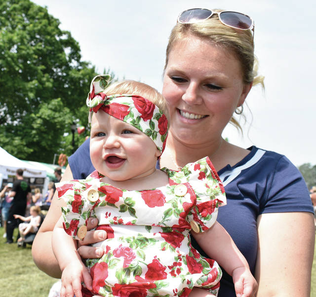 Aliza Rawlins beams at her daughter Charlie, 7 months, dressed up in her strawberry finest. The family, who resides in Brookville brought Charlie for her first visit to the Troy Strawberry Festival.