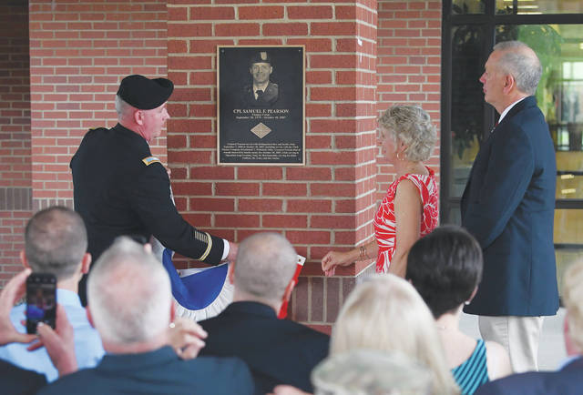 Photo courtesy of the U.S. Army Commandant of the U.S. Army Financial Management School and Chief of the Finance Corps Col. Richard Hoerner (left) along with Carolyn (center) and Randi Pearson unveil a brass plaque bearing Cpl. Samuel F. Pearson's name. The May 3 ceremony dedicated the 369th Adjutant General Battalion dining facility in Cpl. Pearson's name.