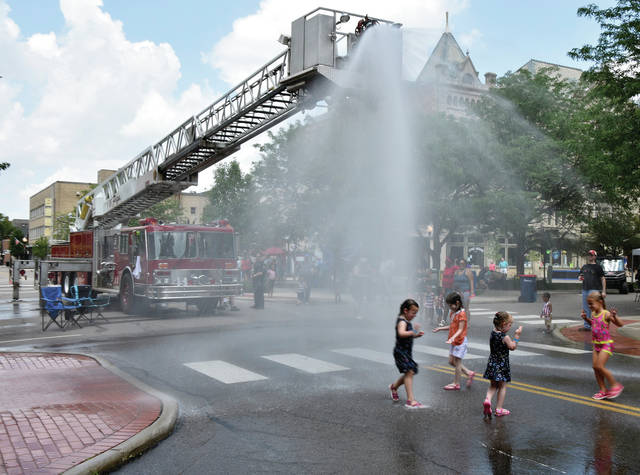 Kids beat the 93-degree temperatures with some help from the Piqua Fire Department during Thursday's annual Piqua 4th Fest celebration.