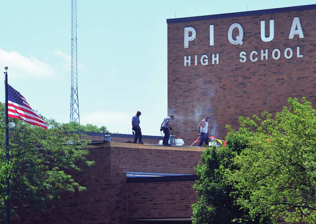 Roofing crews ignore the summer heat as they continue to work on the roof at Piqua High School on Tuesday. ©2019 Miami Valley Today. All rights reserved