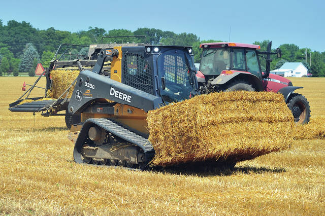 Paige Pence uses a skid-loader to transport and stack bales of straw as another worker from Brent Pence Farms operates the baler behind her in a field near Piqua High School on Tuesday morning. ©2019 Miami Valley Today. All rights reserved