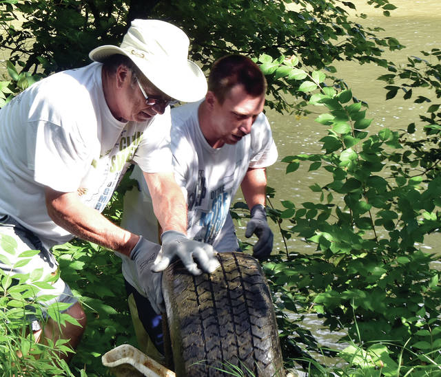 Steve Schmidlapp, left, and Brad Elliott bring an old tire, along with other trash up the bank of the Great Miami River north of Piqua on Saturday during the annual POWW river cleanup. ©2019 Miami Valley Today. All rights reserved