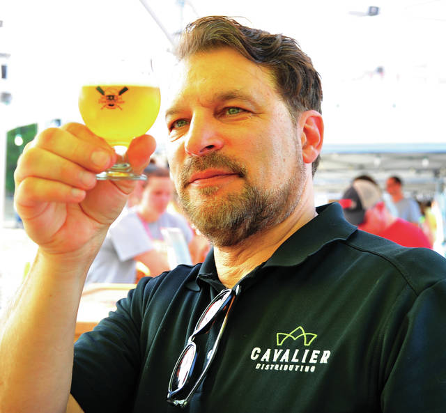 Mike Ullery | Miami Valley Sunday News Jim Witmer of Troy checks the clarity of a brew during the 2018 Down the River, Down a Beer at Lock 9 Park in Piqua.