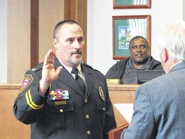 Sam Wildow | Miami Valley Today Piqua Chief of Police Rick Byron takes his oath of office (front left), officially assuming his new role of chief of police for Piqua Police Department, during the Piqua City Commission meeting on Tuesday evening.