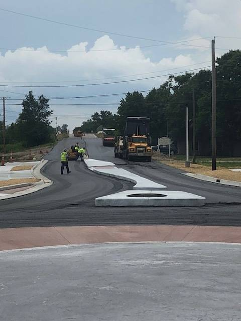 Construction crews add a layer of asphalt to McKaig Road. The roundabout project is expected to be complete mid-August.
