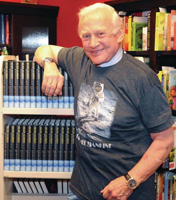 "Mike Ullery | NAHF Photo Edwin ""Buzz"" Aldrin models a new t-shirt while standing near copies of his latest book at Books & Company at The Greene on July 17, 2009. Aldrin, whose Apollo 11 mission in July of 1969 with Neil Armstrong and Michael Collins was, along with Armstrong, one of the first two humans to land on the moon, and the second human being to set foot on the lunar surface."
