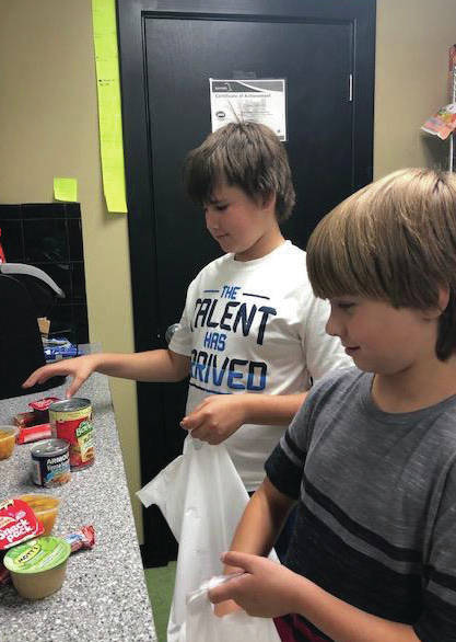 "From left, Dallas Swinehart and Gus Weaver, both 11, help fill ""Weekend Bags"" for food insecure students at the Troy Rec center. The Troy Rec is currently seeking both food and monetary donations to fill bags for approximately 25 students weekly in grades 6-12."