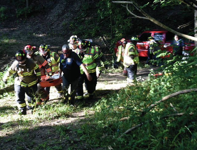 Firefighters from West Milton and Ludlow Falls, along with Union Township medics carry an apparent drug overdose patient from his vehicle at the bottom of a ravine on West State Route 55 near Calumet Road on Sunday morning. ©2019 Miami Valley Today. All rights reserved