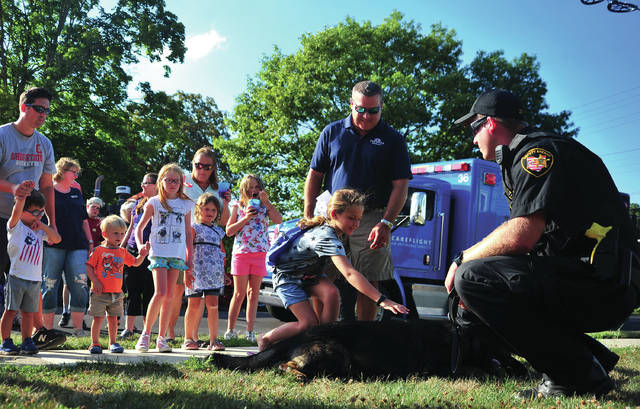 Deputy Ryan Thobe, far right, along with his K-9 partner Vello, greet a line of kids and adults who wanted the chance to pet Vello during Troy's National Night Out event on Tuesday.