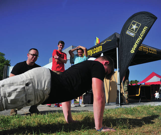 U.S. Army SSGT Justin Creager, left, counts 'em out as Brycen Palivec, 15, of Troy, does a push-up challenge at the Miami County Fair on Friday.