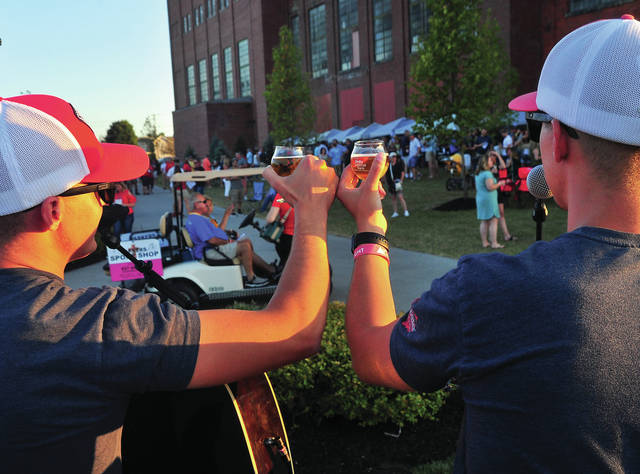 Twins Justin and Jared Younce, aka Reflektion, take a break from their music to offer a toast during Saturday's Down A River Down A Beer event in Piqua.