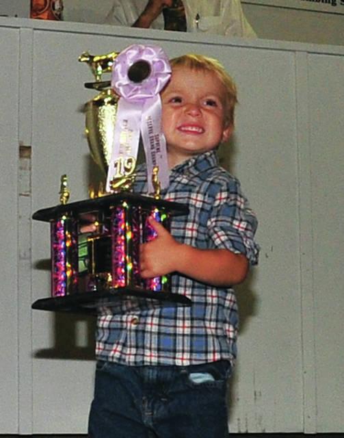 Colby Shellenberger, 3, of Pleasant Hill was all smiles as he helped out in holding trophies in the sale ring at the Miami County Fair Sale of Champions on Wednesday.