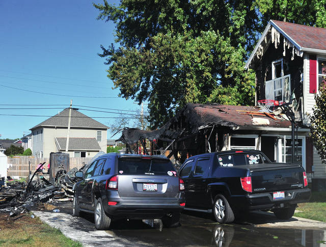The charred remains of a Covington garage sits near a pair of damaged vehicles and a pair of damaged homes on Wall Street following a Saturday morning fire in Covington.