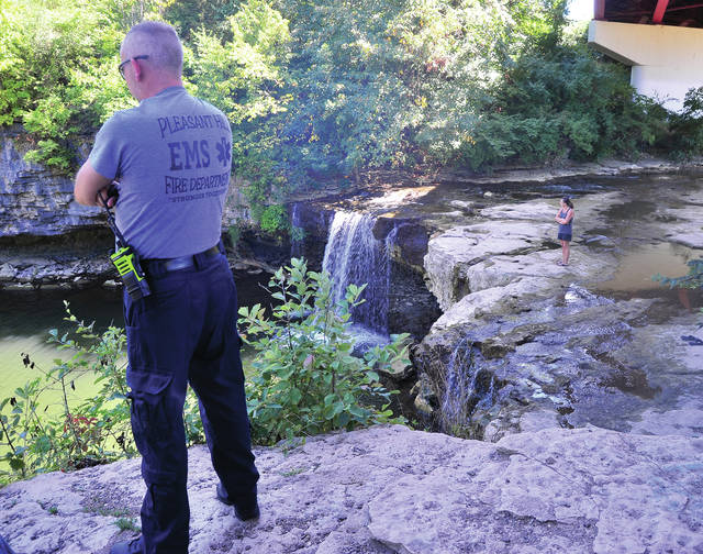 An EMS worker from Pleasant Hill, left, and a neighbor who initially responded to cries for help, look on as recovery efforts get underway for a drowning victim at Ludlow Falls on Thursday afternoon.