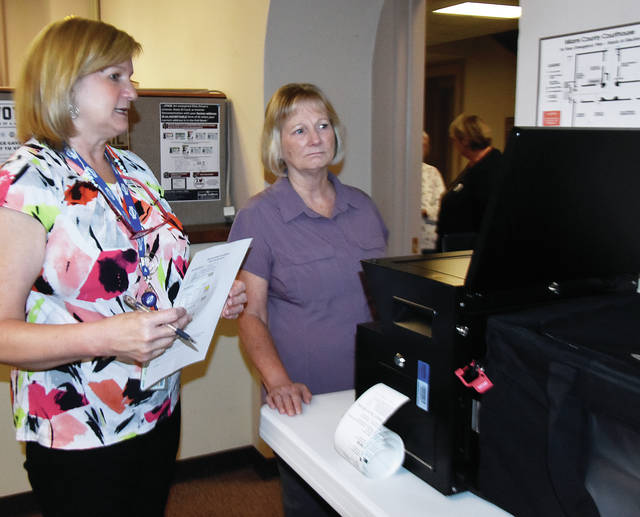 Jill Grimes of Concord Twp. operates a scanner that counts ballots as Laura Bruns, Director of the Miami County Board of Elections looks on during Thursday's mock election to test Miami County's new voting equipment.