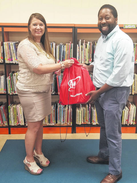 Provided photo Tricia Studebaker, (left) manager of the AAA Troy location, presents the donations from the AAA School Supply Drive to Maurice Sadler, principal of Heywood Elementary, Troy.