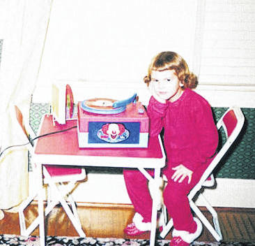 A young Terri Hemmert sits in front of her first record player.