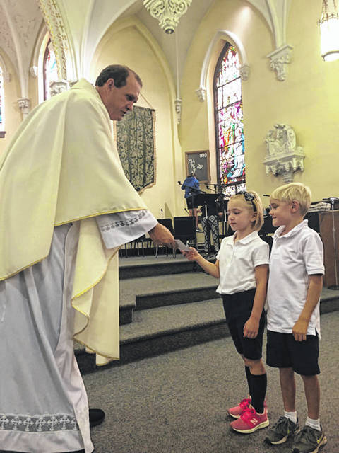 "St. Patrick Catholic Church's Father Eric Bowman hands a pencil to Allie Gutman, 5, following Friday's Mass service. Allie, as well as Daniel Boeckman, 5, are kindergarten students. Father Bowman held a ""Blessing of the pencils"" for each student to carry with them throughout the school year. The St. Patrick Friends and Alumni organization provided the pencils for the school."