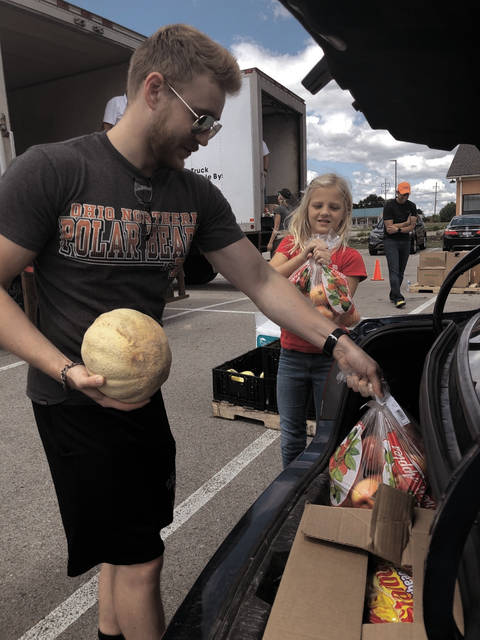 "From left, Connor Bowers, 23, of Sidney, and Blakely Barton, 10, of Tipp City, load fresh fruit into the trunk of a car on Aug. 24 at the Piqua Bistro. The Miami County Food Insecurity committee and Shared Harvest held a ""pop-up pantry"" for Miami County residents. The distribution event had 145 vehicles drive-through to receive fresh produce and food items for their household."