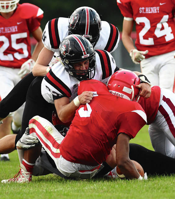 Ben Robinson|GoBuccs.com Covington's Trentin Alexander and Josh Latimer combine for a tackle Friday night.