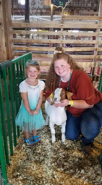 Everly Comer, 4, of Casstown and Eryn Oldham, 18, of West Milton, are pictured with Oldham's goat Tucker. The Comer family bought the goat at Thursday's fair sale for their daughter for a pet.