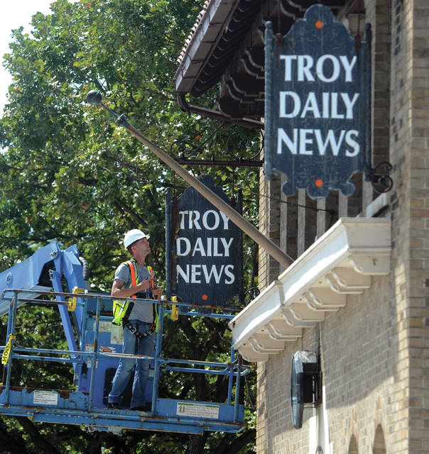 Austin Evans of Level M.B. Construction of Troy begins removing the <em>Troy Daily News</em> signs from the front of 224 S. Market St. on Wednesday afternoon. The <em>Troy</em><em> Daily News/Piqua Daily </em><em>Call</em>, now known as <em>Miami</em><em> Valley </em><em>Today</em>, is moving to their new offices located at 1001 N. County Road 25-A, across from the Miami County Fairgrounds, in Troy, in mid-September.
