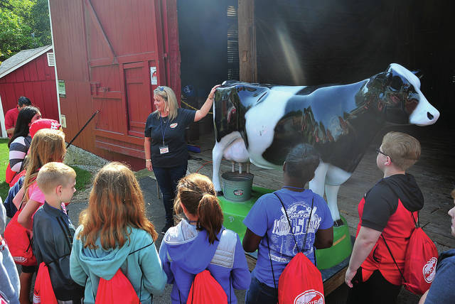 Hartzell volunteer Jennifer Hughes explains dairy farming and milk production to fifth grade students from Piqua Central Intermediate School during the annual Down on the Farm Day at the Miami County Park District Lostcreek Reserve on Friday. The annual event is sponsored by Hartzell in Piqua with a number of their employees attending the event to volunteer to share their knowledge with students. ©2019 Miami Valley Today. All rights reserved