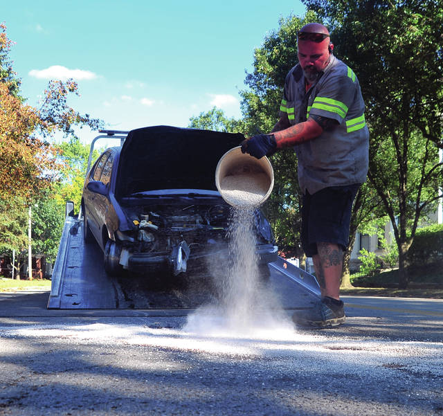 Doug Kerrigan of Bushnells Towing spreads floor dry to soak up fluids left by a vehicle involved in several hit-skip crashes in Piqua on Tuesday afternoon.