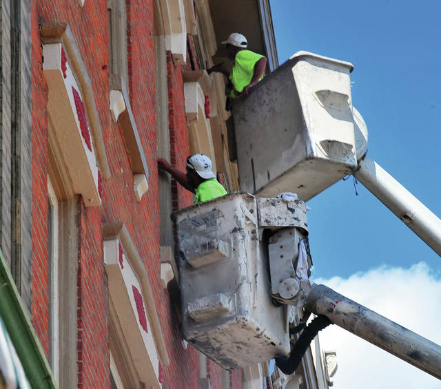 Rob Werst and Shane McKenna of Brian Bros. Painting and Restoration are hard at work, several stories in the air, on the Barclay's building in downtown Piqua on Monday working on giving the building a new paint job while also doing some restoration work. ©2019 Miami Valley Today. All rights reserved.