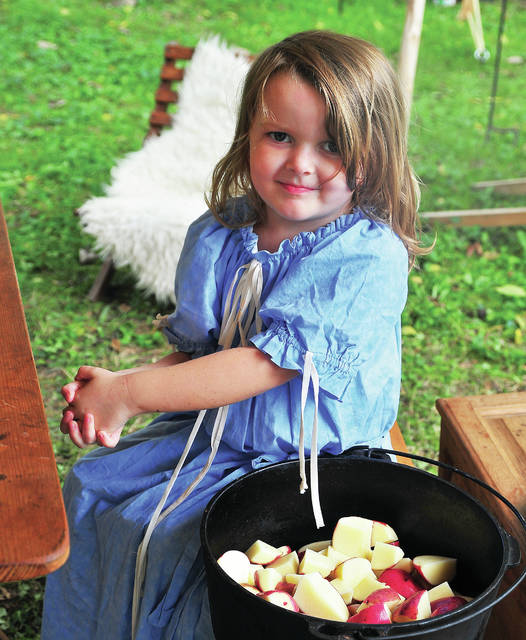 Raycelynn Sage, 4, of Piqua helps her grandmother prepare apples for supper in their camp at Fort Rowdy on Sunday. ©2019 Miami Valley Today. All Rights reserved