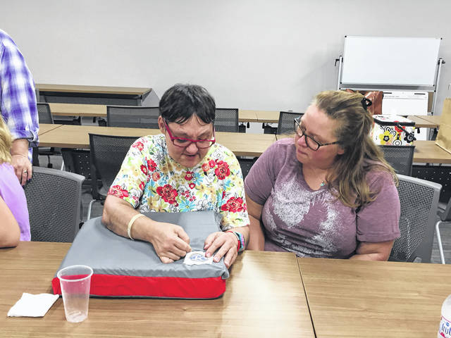 Provided photo DSP Tina Osgood (right) as she watches Paula Bertrand of Troy work on a craft project at Riverside.