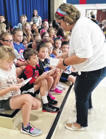 Springcreek Elementary teacher Michelle Robbins passes out Scholastic books recently to, from front left, Karter Hilliard, David Pitman, and Savannah Gress, along with other third-graders. Thanks to the efforts of Robbins and several other Piqua teachers, the entire third grade class was sponsored and will receive a book from the Scholastic Book Club each month for the entire school year.