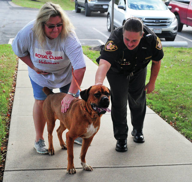 MARS volunteer Jodi Daugherty and Deputy Sarah Fraley admire one of the dogs at the Miami County Animal Shelter on Wednesday morning. Volunteers from Royal Canin, a division of MARS, the company that produces Iames dog food in Lewisburg, were at the shelter to work on a number of projects, including weeding and mulching, power washing, and helping to care for animals.
