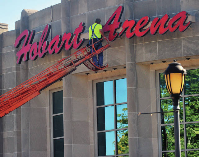 Aaron Hillis from Kessler Sign Service replaces neon lighting and cleans the sign on the front of Hobart Arena on Thursday.