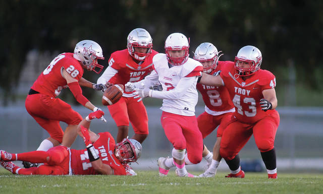 Lee Woolery|Miami Valley Today Troy's Dawson Roby (28), Evan Jones (41), J.J. McCoy (5), Josh Mayfield (8) and Elijah Atkins (43) swarm the ball as a Stebbins receiver fumbles Friday at Troy Memorial Stadium.