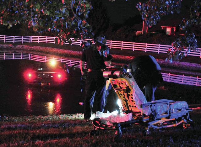 Troy police and medics assist a female passenger of a truck that ran into a retention pond off Stanfield Road while allegedly fleeing police on Wednesday evening.