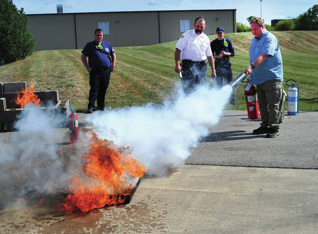 Bob Alexander of Coate Concrete in West Milton demonstrates the use of a fire extinguisher as Piqua Assistant Fire Chief Lee Adams looks on during a Thursday Miami County Safety Council Meeting at Romer's Catering Learning Center as part of National Fire Prevention Week. The event was sponsored by the Piqua Area Chamber of Commerce.