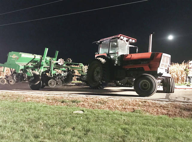 A large tractor and planter rest on Mowry Road following a Monday evening fatal crash involving the tractor and SUV.