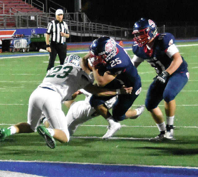 Ca'ron Coleman (25) breaks the tackle of Connor Mills on the way to the end zone Friday night in Piqua's 21-7 win over Greenville at Alexander Stadium/Purk Field.