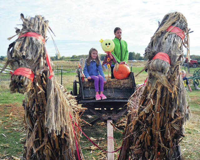 Ellison Stump, 8, and her 10-year-old sister Evelline, of Vandalia, pose as their mom Svetlana, takes a photo recently at Fulton Farms near Troy. Fall activities, like hayrides, continue through this weekend from 11 a.m. to 5 p.m. on Saturday and Sunday. Visit fultonfarms.com for more information.