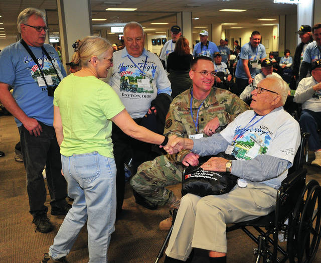 Honor Flight Dayton volunteer Terri Lynn Perkins of Fairborn, front left, greets a veterans as he prepares to board the Honor Flight Dayton charter flight bound for Washington, D.C. on Saturday morning at the Dayton International Airport for the group's last flight of 2019. The final 2019 trip took 106 veterans to see their memorials, including 5 from World War II, 9 from the Korean War, 91 from the Vietnam War, and one Cold War veteran. The oldest veteran on this journey was 95 years old and one of the veterans was involved in World War II, the Korean War, and Vietnam. Honor Flight Dayton will resume their mission of making sure that veterans get to see their memorial in Washington, D.C. again in the spring. Eligible veterans or family members wishing to get their veterans on an Honor Flight trip, or for anyone interested in volunteering with Honor Flight Dayton, please visit www.honorflightdayton.org