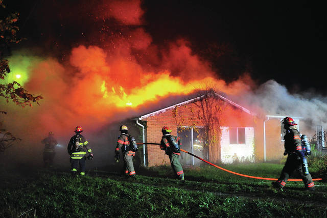 Firefighters from several departments battle a house fire on Monroe-Concord Road on Wednesday night.