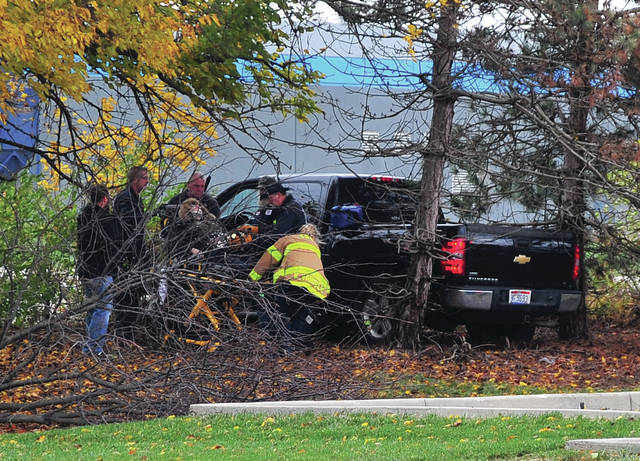 Troy firefighters and medics assist the driver of a pickup truck that crashed at F&P America on Thursday afternoon.