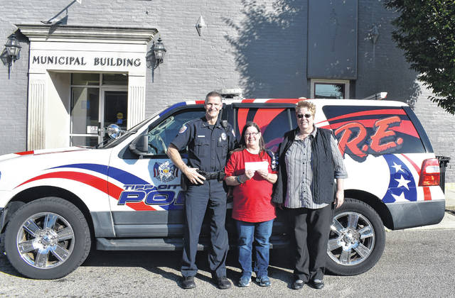 Provided photo Sandy Adkins, center, from the Tipp City American Legion recently presented a donation to Tipp City Police Officer Dan Rittenhouse and Tipp-Monroe Community Services Director Kathy Taylor.