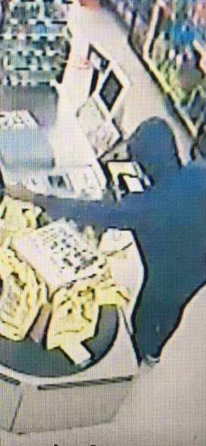 Courtesy of the Piqua Police Department The suspect in an armed robbery reported at Dollar General in Piqua on Sunday evening seen reaching for a bag of cash on video surveillance.